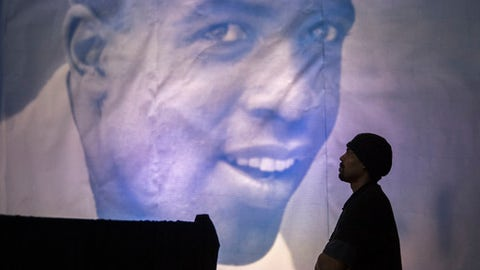 A man is framed by a giant poster of Jackie Robinson as he watches the ceremonial ground breaking for the Jackie Robinson Museum, Thursday, April 27, 2017, in New York. (AP Photo/Mary Altaffer)