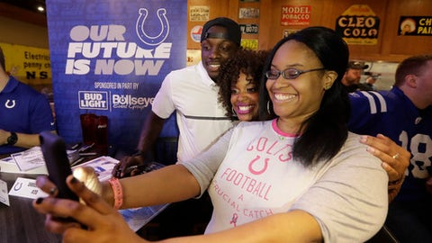 Renee Larson, right, and Paris Carter take a photo with Indianapolis Colts' Darius Butler during the NFL football team's draft party Thursday, April 27, 2017, in Indianapolis. (AP Photo/Darron Cummings)