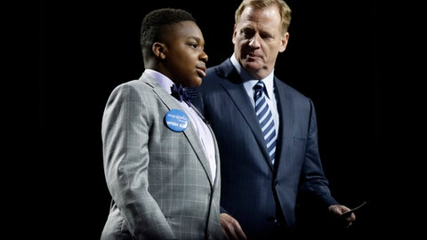 T.J. Owuanibe, 14, left, walks with NFL commissioner Roger Goodell to announce the Baltimore Ravens' selection during the first round of the 2017 NFL football draft, Thursday, April 27, 2017, in Philadelphia. (AP Photo/Matt Rourke)