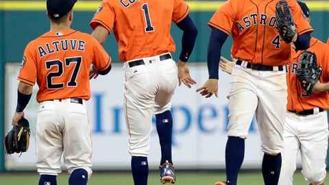 Houston Astros' George Springer (4), =Carlos Correa (1) and Jose Altuve (27) celebrate after beating the Oakland Athletics in a baseball game Friday, April 28, 2017, in Houston. The Astros won 9-4. (AP Photo/David J. Phillip)