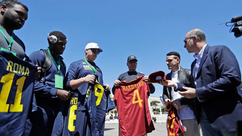 Michigan football team coach Jim Harbaugh, third from right is presented with a Roma jersey by Roma midfielder Alessandro Florenzi, second from right, prior to a training session at Rome's Stadio Dei Marmi, Saturday, April 29, 2017. (AP Photo/Alessandra Tarantino)