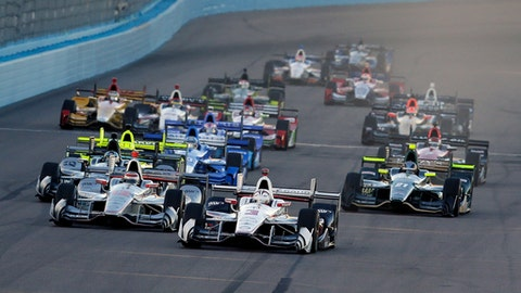 Helio Castroneves (3) leads the field on the opening lap during the IndyCar auto race Saturday, April 29, 2017, at Phoenix International Raceway in Avondale, Ariz. (AP Photo/Rick Scuteri)