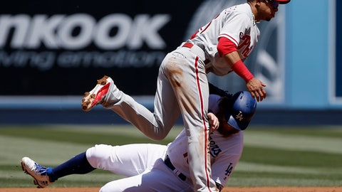 Philadelphia Phillies second baseman Cesar Hernandez, above, follows through after throwing to first to get Los Angeles Dodgers' Yasiel Puig for a double play, after forcing out the sliding Justin Turner, below, during the first inning of a baseball game in Los Angeles, Sunday, April 30, 2017. (AP Photo/Alex Gallardo)