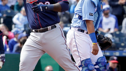 Minnesota Twins' Miguel Sano, left, crosses the plate past Kansas City Royals catcher Salvador Perez after hitting a three-run home run during the third inning of a baseball game Sunday, April 30, 2017, in Kansas City, Mo. (AP Photo/Charlie Riedel)