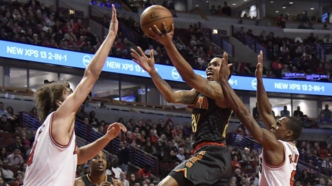 Apr 1, 2017; Chicago, IL, USA; Atlanta Hawks forward Kent Bazemore (24) goes to the basket as Chicago Bulls guard Rajon Rondo (R) and  center Robin Lopez (8) defend him during the second half at the United Center.  The Bulls won 106-104. Mandatory Credit: David Banks-USA TODAY Sports