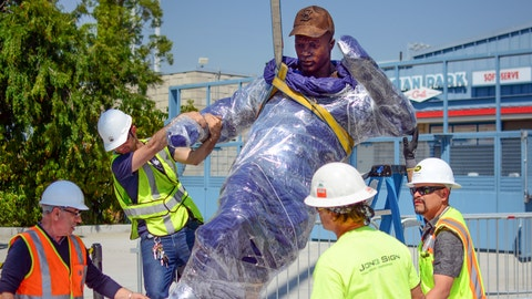 In this April 10, 2017 photo provided by the Los Angeles Dodgers, workers install a bronze statue of Dodgers legend Jackie Robinson outside Dodger Stadium in Los Angeles. Robinson was the first black man to play major league baseball, ending six decades of racial segregation, and a first-ballot Hall of Famer. He will be the first to be honored with a statue at the Dodgers' Los Angeles home when it will be unveiled Saturday, April 15, 2017, on the 70th anniversary of his debut with the Brooklyn Dodgers. (Rowan Kavner/Los Angeles Dodgers via AP)