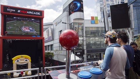 """Attendees play the Electronic Arts Inc. (EA) Sports """"Madden NFL 2017"""" video game on a giant screen at the Doritos #MixArcade fan experience during the E3 Electronic Entertainment Expo in Los Angeles, California, U.S., on Wednesday, June 15, 2016. E3, a trade show for computer and video games, draws professionals to experience the future of interactive entertainment as well as to see new technologies and never-before-seen products. Photographer: Patrick T. Fallon/Bloomberg via Getty Images"""