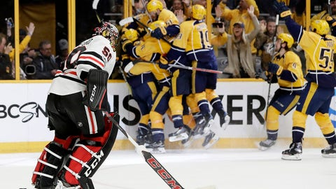 Chicago Blackhawks goalie Corey Crawford (50) skates to the bench as Nashville Predators players celebrate after Predators left wing Kevin Fiala scored the winning goal during overtime in Game 3 of a first-round NHL hockey playoff series Tuesday, April 18, 2017, in Nashville, Tenn. The Predators won 3-2 to take a 3-0 lead in the series. (AP Photo/Mark Humphrey)