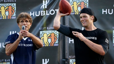 New England Patriots' Tom Brady, right, tosses a ball beside Anthony Kennedy Shriver during the Best Buddies Challenge charity football game  in Boston, Friday, May 29, 2015. (AP Photo/Michael Dwyer)