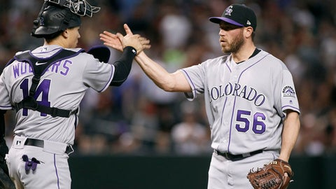 Colorado Rockies' Greg Holland (56) is congratulated by Tony Wolters after pitching the ninth inning against the Arizona Diamondbacks during a baseball game, Saturday, April 29, 2017, in Phoenix. The Rockies won 7-6. (AP Photo/Ralph Freso)