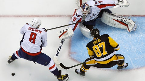 Pittsburgh Penguins' Sidney Crosby (87) can't get a shot off in front of Washington Capitals goalie Braden Holtby (70) with Alex Ovechkin (8) defending during the first period of Game 3 in an NHL Stanley Cup Eastern Conference semifinal hockey game in Pittsburgh, Monday, May 1, 2017. Crosby was injured on the play and did not return to the game. The Capitals won in overtime 3-2. (AP Photo/Gene J. Puskar)