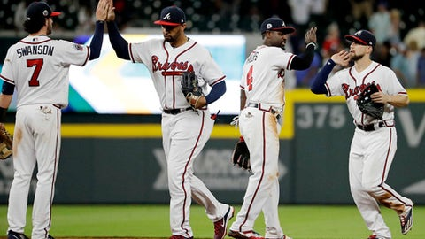 Atlanta Braves' Dansby Swanson, Matt Kemp, Brandon Phillips and Ender Inciarte from left, greet one another after the Braves defeated the New York Mets 9-7 in a baseball game in Atlanta, Tuesday, May 2, 2017. (AP Photo/David Goldman)