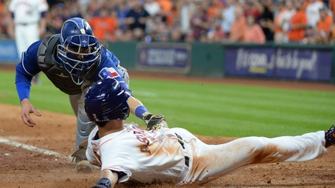 Houston Astros' Norichika Aoki slides safely into home before the tag by Texas Rangers catcher Jonathan Lucroy during the sixth inning of a baseball game Wednesday May 3, 2017, in Houston. (AP Photo/George Bridges)