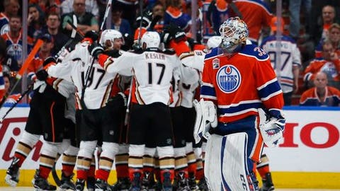 Anaheim Ducks celebrate their overtime victory as Edmonton Oilers goalie Cam Talbot, front, skates past after Game 4 of an NHL hockey second-round playoff series, Wednesday, May 3, 2017, in Edmonton, Alberta. Anaheim won 4-3. (Jeff McIntosh/The Canadian Press via AP)
