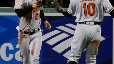 Baltimore Orioles right fielder Joey Rickard, left, is congratulated by center fielder Adam Jones after he caught a fly ball by Boston Red Sox's Andrew Benintendi in the seventh inning of a baseball game at Fenway Park, Thursday, May 4, 2017, in Boston. (AP Photo/Elise Amendola)