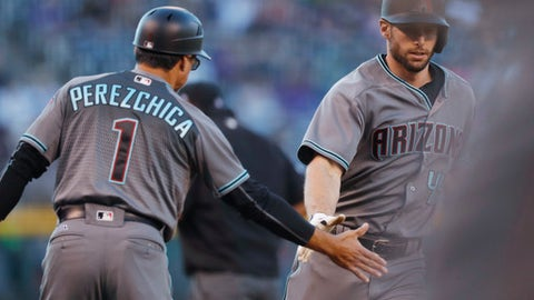 Arizona Diamondbacks third base coach Tony Perezchica, left, congratulates Paul Goldschmidt who circles the bases after hitting a solo home run off Colorado Rockies relief pitcher German Marquez in the first inning of a baseball game Friday, May 5, 2017, in Denver. (AP Photo/David Zalubowski)