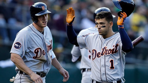 Detroit Tigers' Jose Iglesias, right, and Jim Adduci celebrate after scoring against the Oakland Athletics in the second inning of a baseball game, Saturday, May 6, 2017, in Oakland, Calif. Both scored on a triple by Tigers' Andrew Romine. (AP Photo/Ben Margot)