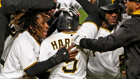 Pittsburgh Pirates' Josh Harrison, 5, is mobbed by teammates after driving in the winning run with a single off Milwaukee Brewers relief pitcher Carlos Torres in the tenth inning of a baseball game in Pittsburgh, Saturday, May 6, 2017. The Pirates won 2-1. (AP Photo/Gene J. Puskar)