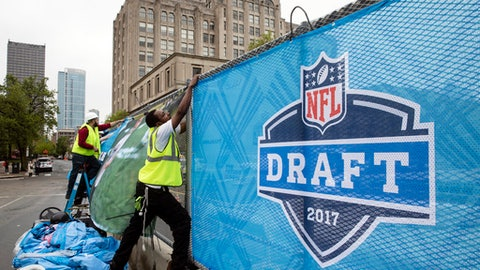 FILE - In this Wednesday, April 26, 2017, Workers make preparations ahead of the 2017 NFL football draft, in Philadelphia. A North Carolina financial planner's prison sentence for stealing from pro football players offers a cautionary tale to young athletes set to make millions after the NFL draft.  The instant millionaires may know where they'll be playing professional football, but they're still figuring out how to manage their new wealth. (AP Photo/Matt Rourke, File)