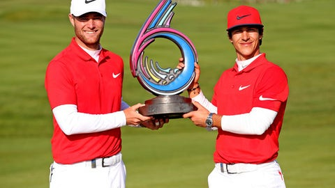 Denmark's Thorbjorn Olesen, right, and Lucas Bjerregaard celebrate with the trophy after the winning the final during day two of the Golf Sixes at the Centurion Club, St Albans England, Sunday May 7, 2017. (Steven Paston/PA via AP)