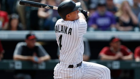 Colorado Rockies' Pat Valaika follows the flight of his two-run home run off Arizona Diamondbacks relief pitcher J.J. Hoover in the sixth inning of a baseball game Sunday, May 7, 2017, in Denver. (AP Photo/David Zalubowski)
