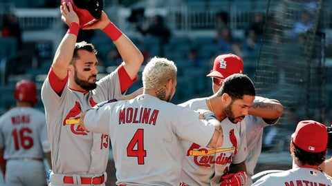 St. Louis Cardinals' Tommy Pham (28) is greeted at the dugout by teammates Matt Carpenter, left, and Yadier Molina (4) after hitting a two-run home run in the 14th inning of a baseball game against the Atlanta Braves, Sunday, May 7, 2017, in Atlanta. The Cardinals won 6-4. (AP Photo/John Bazemore)