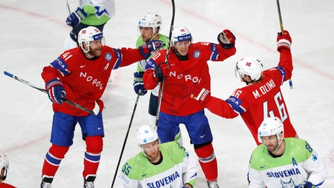 Norway's Mathis Olimb, right, celebrates with teammates Patrick Thoresen, left, and Ken Andre Olimb, center, after scoring his sides first goal during the Ice Hockey World Championships group B match between Slovenia and Norway in the AccorHotels Arena in Paris, France, Tuesday, May 9, 2017. (AP Photo/Petr David Josek)