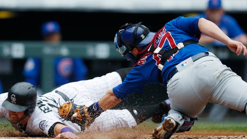 Colorado Rockies' Mark Reynolds, left, slides safely into home plate to score on an single by Trevor Story as Chicago Cubs catcher Miguel Montero turns to apply a late tag in the fourth inning of the first baseball game of a doubleheader Tuesday, May 9, 2017, in Denver. (AP Photo/David Zalubowski)