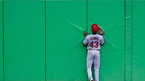 St. Louis Cardinals center fielder Magneuris Sierra stands at the wall as he watches a ball hit by Miami Marlins' Christian Yelich sail over the wall for a home run during the first inning of a baseball game, Wednesday, May 10, 2017, in Miami. (AP Photo/Wilfredo Lee)
