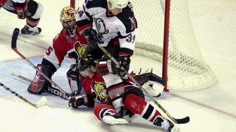 Buffalo Sabres left winger Jason Botterill (34) tries to get his stick on the puck while being held by Ottawa Senators defenseman Julien Vauclair (42) as Senators goalie Jani Hurme (35) protects the front of the net in the first period of a preseason game Saturday, Sept. 21, 2002, in Buffalo. (AP Photo/Don Heupel)