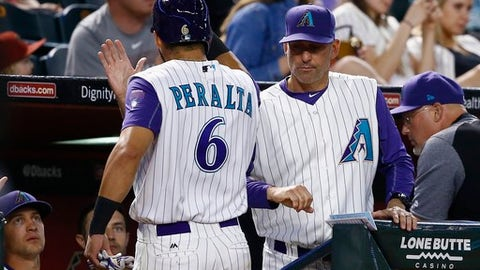Arizona Diamondbacks' David Peralta (6) celebrates his run scored against the Pittsburgh Pirates with manager Torey Lovullo, right, and Nick Ahmed, left, during the third inning of a baseball game Thursday, May 11, 2017, in Phoenix. (AP Photo/Ross D. Franklin)