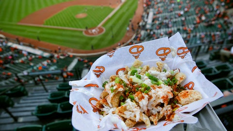 This May 8, 2017, photo shows a Crabmeat Pork Rind Chipper at Oriole Park at Camden Yards before a baseball game between the Washington Nationals and the Baltimore Orioles in Baltimore. It contains pork rinds topped with cheese sauce, crab meat, Old Bay seasoning, and scallions. (AP Photo/Patrick Semansky)