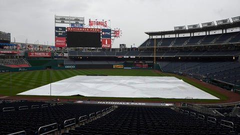 The tarp lies on the baseball field, Friday, May 12, 2017, in Washington. The baseball game between the Washington Nationals and the Philadelphia Phillies was postponed due to inclement weather. (AP Photo/Nick Wass)