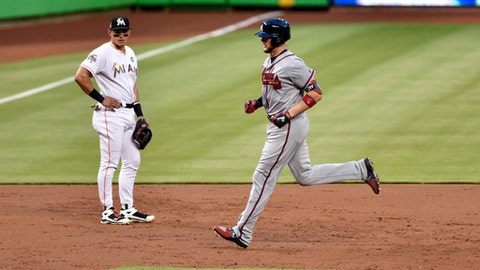 Atlanta Braves' Tyler Flowers, right, runs past Miami Marlins third baseman Derek Dietrich after hitting a home run in the second inning of a baseball game Friday, May 12, 2017, in Miami. (AP Photo/Gaston De Cardenas)