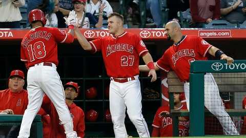 Los Angeles Angels' Mike Trout (27), Albert Pujols, right, congratulate Luis Valbuena (18) with manager Mike Scioscia, left, and Dino Ebel watching, after Valbuena hit a solo home run during the second inning of a baseball game against the Detroit Tigers in Anaheim, Calif., Friday, May 12, 2017. (AP Photo/Alex Gallardo)