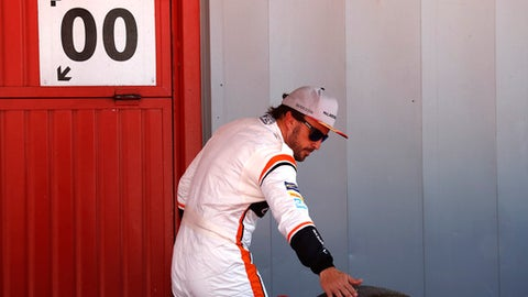 Mclaren driver Fernando Alonso of Spain touches a tire in the team garage after the qualifying session for the Spanish Formula One Grand Prix at the Barcelona Catalunya racetrack in Montmelo, Spain, Saturday, May 13, 2017. The Spanish Formula One Grand Prix will take place on Sunday. (AP Photo/Manu Fernandez)