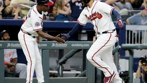 Atlanta Braves' Matt Kemp, right, high-fives third base coach Ron Washington after hitting a home run in the third inning of a baseball game against the Washington Nationals in Atlanta, Friday, May 19, 2017. (AP Photo/David Goldman)
