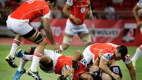 Yoshitaka Tokunaga of Japan's Sunwolves falls to the ground after being tackled by Lorens Adriaanse of South Africa's Sharks during their Super Rugby match on Saturday, May 20, 2017, in Singapore. (AP Photo/Wong Maye-E)