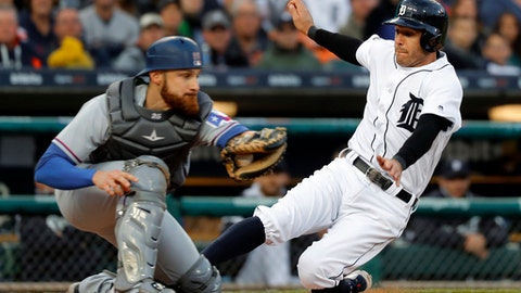 Detroit Tigers' Ian Kinsler, right, slides safely into home plate as Texas Rangers catcher Jonathan Lucroy receives the throw in the third inning of a baseball game in Detroit, Saturday, May 20, 2017. (AP Photo/Paul Sancya)