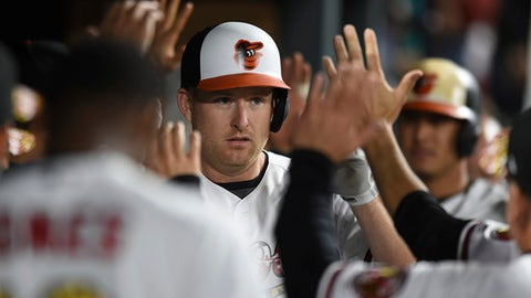 Baltimore Orioles' Mark Trumbo is congratulated in the dugout after hitting a two-run home run against the Toronto Blue Jays in the fifth inning of a baseball game, Saturday, May 20, 2017, in Baltimore. (AP Photo/Gail Burton)