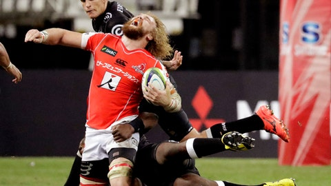 In this Saturday, May 20, 2017 photo, Willem Britz of Japan's Sunwolves gets tackled by Tendai Mtawarira of South Africa's Sharks during their Super Rugby match in Singapore. (AP Photo/Wong Maye-E, File)