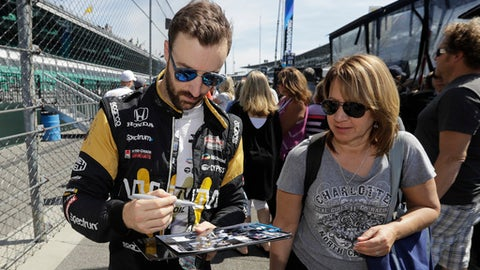 James Hinchcliffe, left, of Canada, gives autographs to fans following a practice for the Indianapolis 500 IndyCar auto race at Indianapolis Motor Speedway, Monday, May 22, 2017, in Indianapolis. (AP Photo/Darron Cummings)