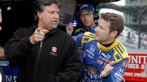 FILE - In this May 20, 2016, file photo, Marco Andretti, right, talks with car owner and father Michael Andretti during a practice session for the Indianapolis 500 auto race at Indianapolis Motor Speedway in Indianapolis. Michael Andretti needed some assurances before running six cars in this year's Indianapolis 500.  He also needed some help. But aside from finding extra crew members and sponsorship, the biggest challenge of this week may be communication.  (AP Photo/Michael Conroy, File)