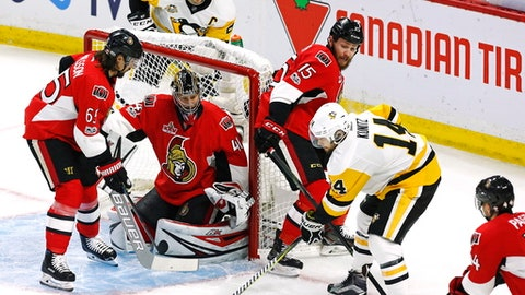 Pittsburgh Penguins left wing Chris Kunitz (14) shoots on Ottawa Senators goalie Craig Anderson (41) as Senators defenseman Erik Karlsson (65) and Senators centre Zack Smith (15) defend during the first period of game six of the Eastern Conference final in the NHL Stanley Cup hockey playoffs in Ottawa on Tuesday, May 23, 2017. (Fred Chartrand/The Canadian Press via AP)