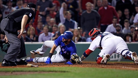 Boston Red Sox catcher Sandy Leon, right, makes the tag, catching Texas Rangers' Nomar Mazara trying to score on a double by Jonathan Lucroy during the seventh inning of a baseball game at Fenway Park in Boston, Tuesday, May 23, 2017. Umpire Tim Welke, left, called Mazara out on the play, which was upheld after a challenge. (AP Photo/Charles Krupa)