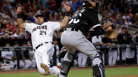 Arizona Diamondbacks' Yasmany Tomas (24) scores on an RBI double by teammate Brandon Drury as Chicago White Sox catcher Kevan Smith (36) waits for the throw during the fourth inning of a baseball game, Tuesday, May 23, 2017, in Phoenix. (AP Photo/Matt York)