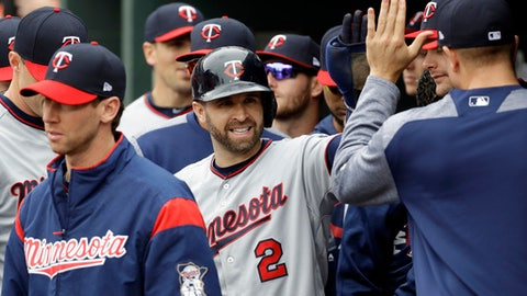 Minnesota Twins' Brian Dozier high-fives teammates in the dugout after scoring on an RBI double by Kennys Vargas in the first inning of a baseball game against the Baltimore Orioles in Baltimore, Wednesday, May 24, 2017. (AP Photo/Patrick Semansky)
