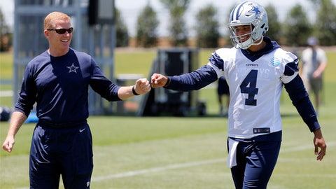 Dallas Cowboys head coach Jason Garrett, left, gets quarterback Dak Prescott (4) a fist bump as the two walk off the field after an NFL football organized team activities practice at the team's training facility, Wednesday, May 24, 2017, in Frisco, Texas. (AP Photo/Tony Gutierrez)