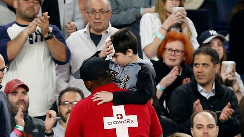Fans applaud as a medical employee carries an injured youngster from the stands after the boy was hit in the head by a piece the Yankees's Chris Carter's bat that split during the seventh inning of a baseball game against the Kansas City Royals at Yankee Stadium in New York, Wednesday, May 24, 2017. (AP Photo/Kathy Willens)