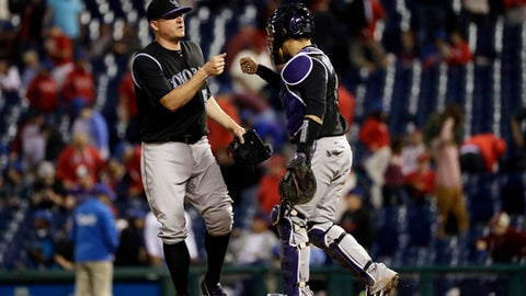 Colorado Rockies relief pitcher Jake McGee, left, and catcher Tony Wolters celebrate after a baseball game against the Philadelphia Phillies, Wednesday, May 24, 2017, in Philadelphia. Colorado won 7-2. (AP Photo/Matt Slocum)